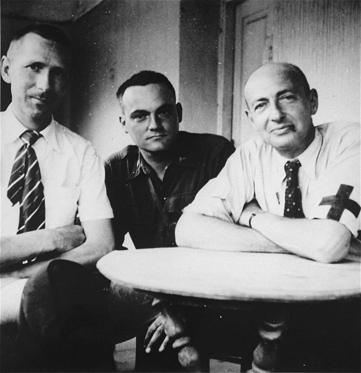 Portrait of three physicians, two of them former concentration camp prisoners, who aided survivors from the Ebensee concentration camp at an American military field hospital.  Pictured are former prisoners, Lt. Col. Sanford of the 30th Field Hospital, originally from Belgium (left), and Dr. Gilbert Debrise (Dreyfus), originally from Paris (middle).