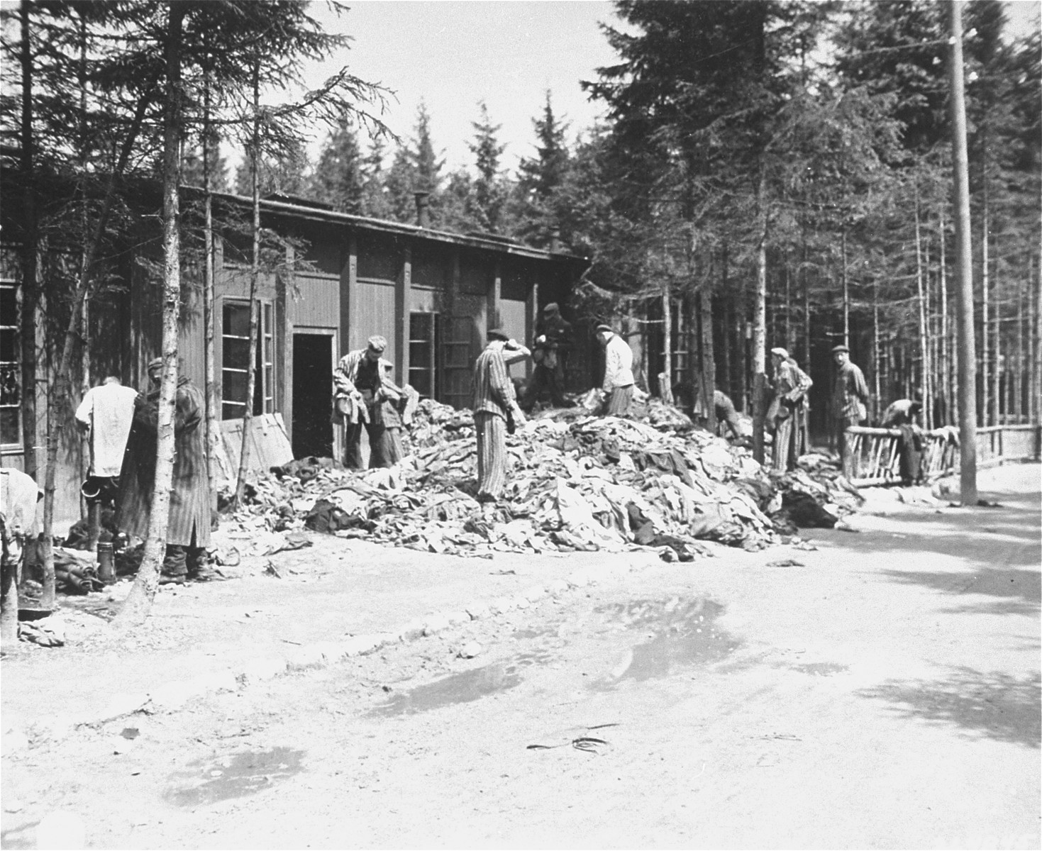 Survivors rummage through piles of clothing outside a barracks in the newly liberated Ebensee concentration camp.