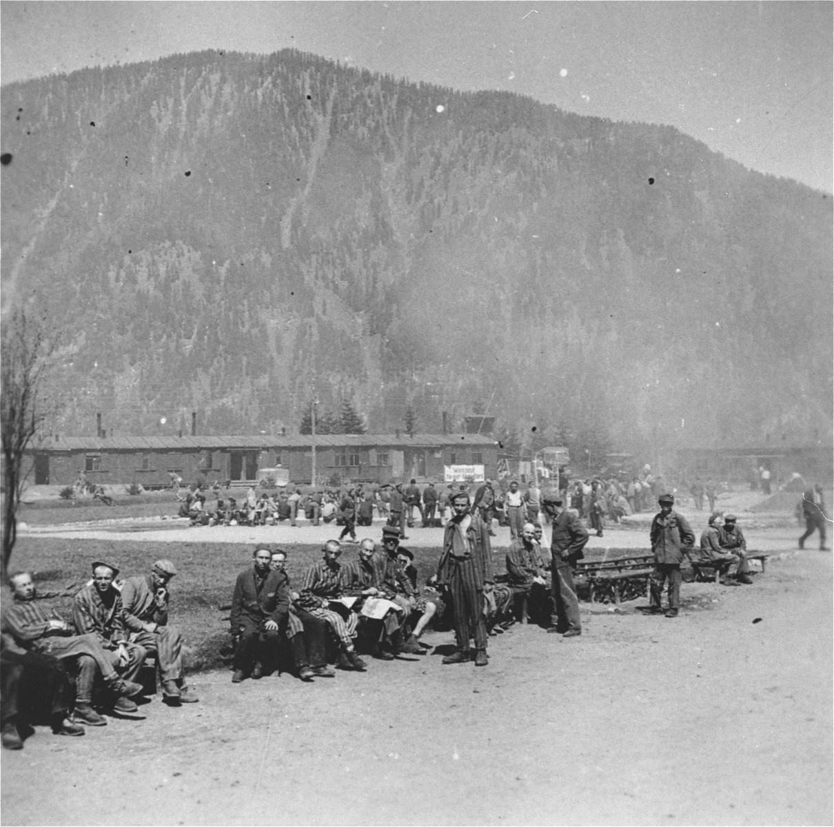 Survivors sit on benches along the perimeter of the former roll call area in the Ebensee concentration camp.