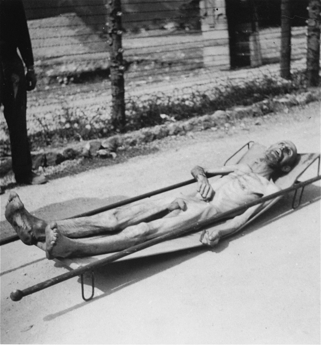 A Hungarian Jewish prisoner who has just died lies on a stretcher in the Ebensee concentration camp.    [This is the probably the same man in WS 06415 before his name and number were written on his chest.]