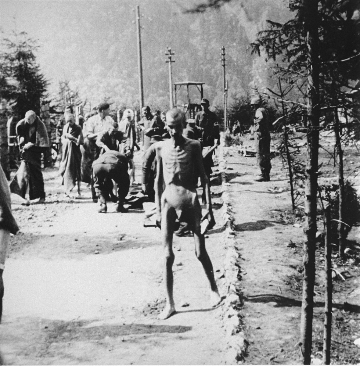 Emaciated survivors walk along a road in the Ebensee concentration camp, past a group of Austrian civilians who have been forcibly brought in to help evacuate survivors who are too weak to walk.