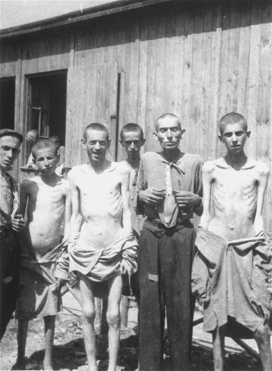 A group of survivors pose in front of a barracks in the newly liberated Ebensee concentration camp.