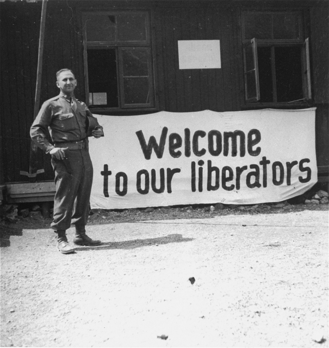 "Eugene Cohen stands in front of a banner offering ""Welcome to our liberators"" in the Mauthausen concentration camp."