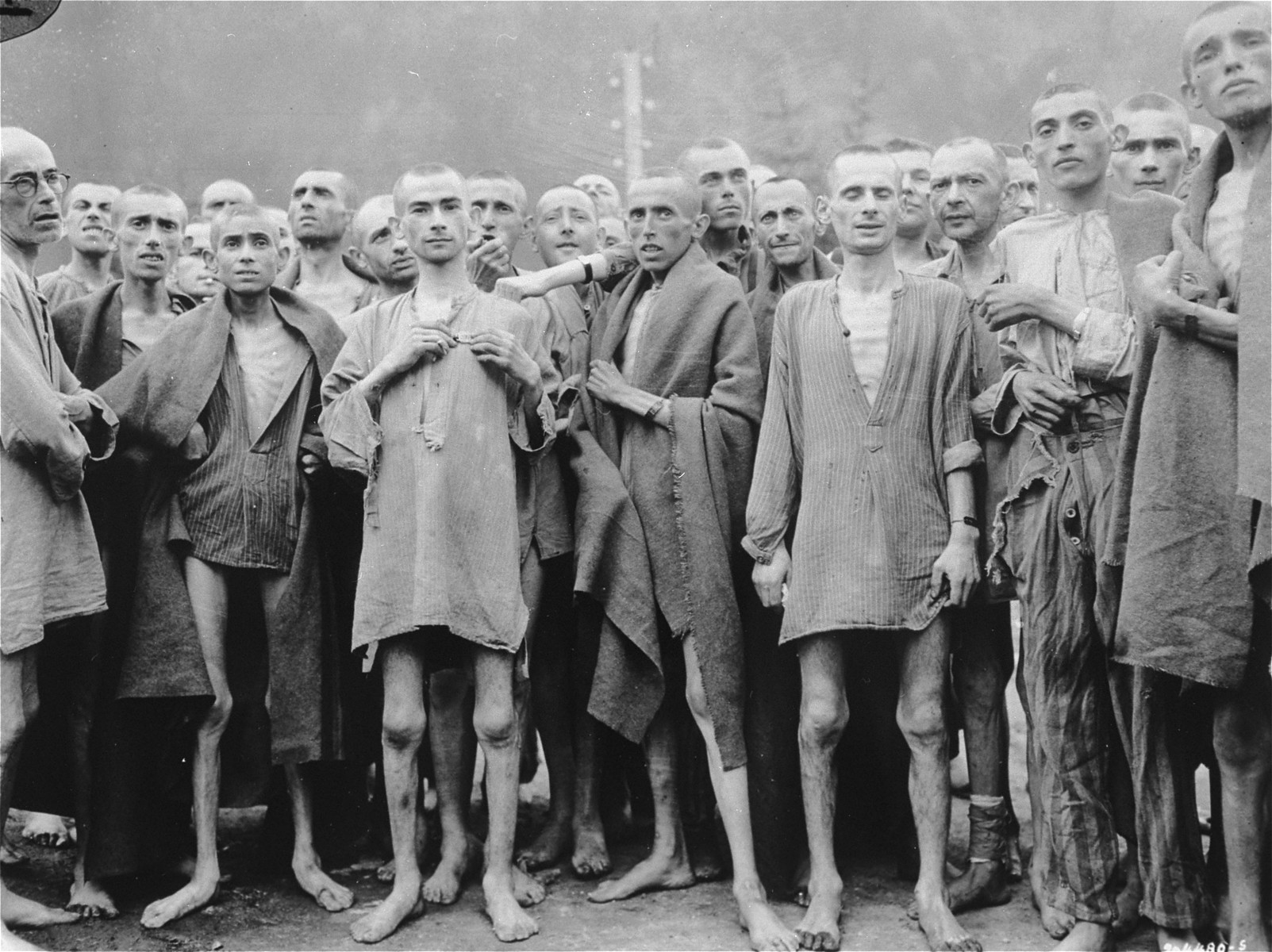 "One day after their liberation, a group of former prisoners at the Ebensee concentration camp pose outside for US Army Signal Corps photographer Arnold Samuelson.  The former prisoners came out of the infirmary barracks in order to be photographed.  Among those pictured is a 21-year old Jewish survivor by the name of Joachim Friedner from Krakow, Poland (center-left holding his metal name tag), and William Hauben (second row from the front between the survivor holding his name tag and the one wearing a blanket).  Bernard Smilovic is located second from the left, first row wearing a blanket.  Original caption reads: "" Starved prisoners, nearly dead from hunger, pose in the Nazi concentration camp in Ebensee, Austria.   In the Austrian Alps the Nazis had one of their largest camps.  Large numbers of inmates were starving to death and dying at the rate of 2000 per week.  The camp was reputedly used for ""Scientific"" experiments.  It was liberated by the 80th Division, 3rd U.S. Army.""   Original caption from donated photograph reads:  ""Starved prisoners, nearly dead from hunger, pose for the photographer in their rags."""