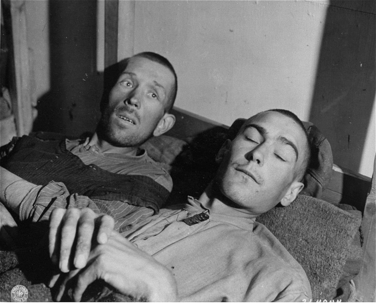 Two survivors rest on a bunk in the infirmary barracks for non-Jewish prisoners in the Ebensee concentration camp.