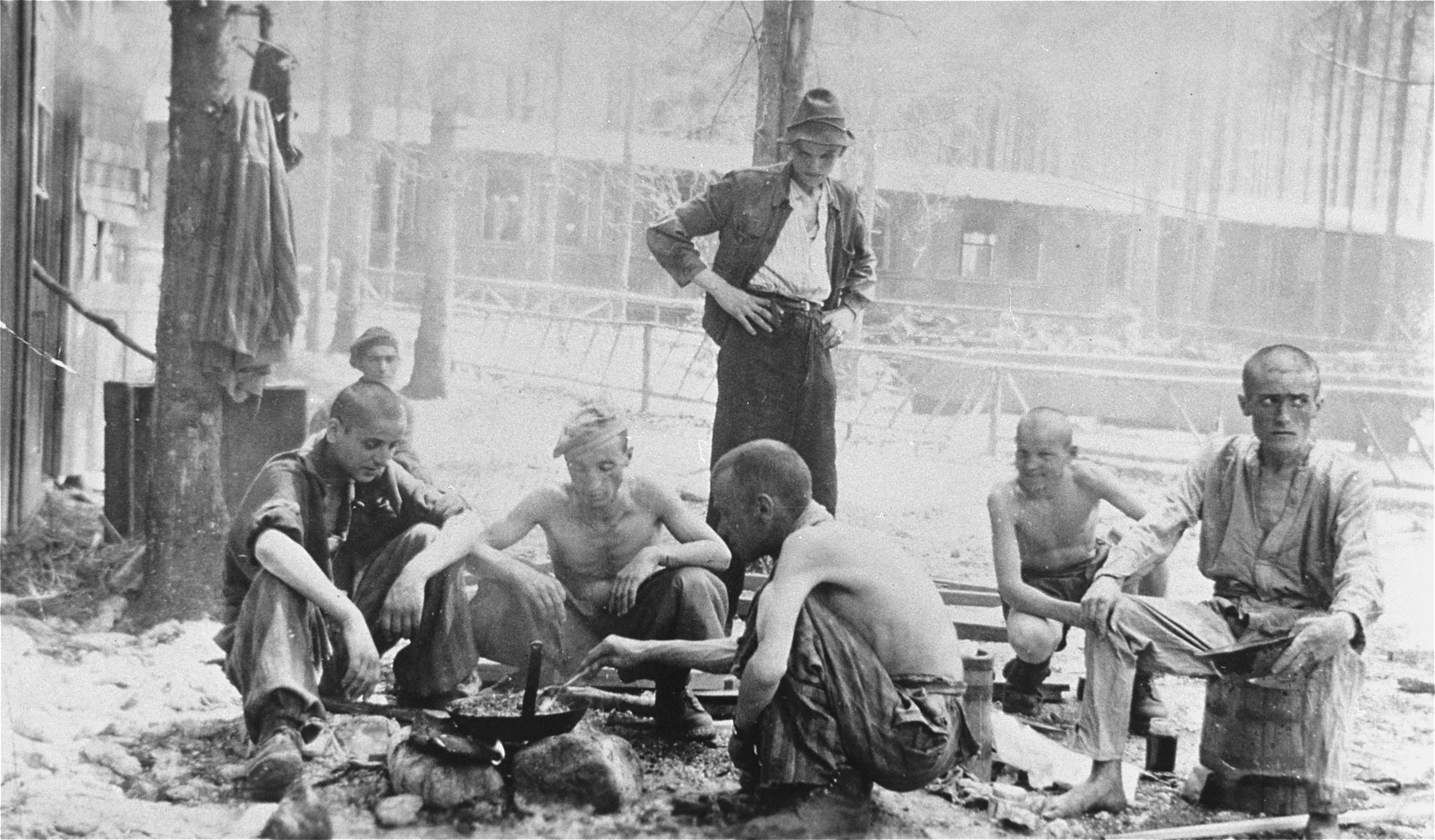 Survivors in Ebensee cook a meal over an open fire.
