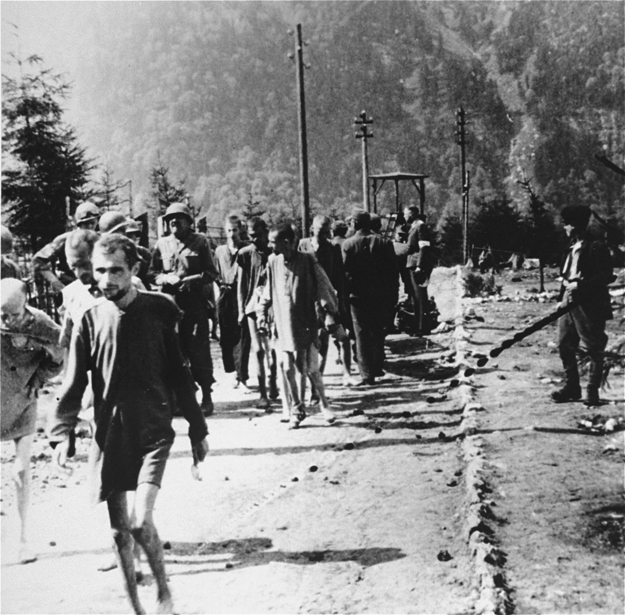 American soldiers walk among emaciated survivors along a road in the Ebensee concentration camp.