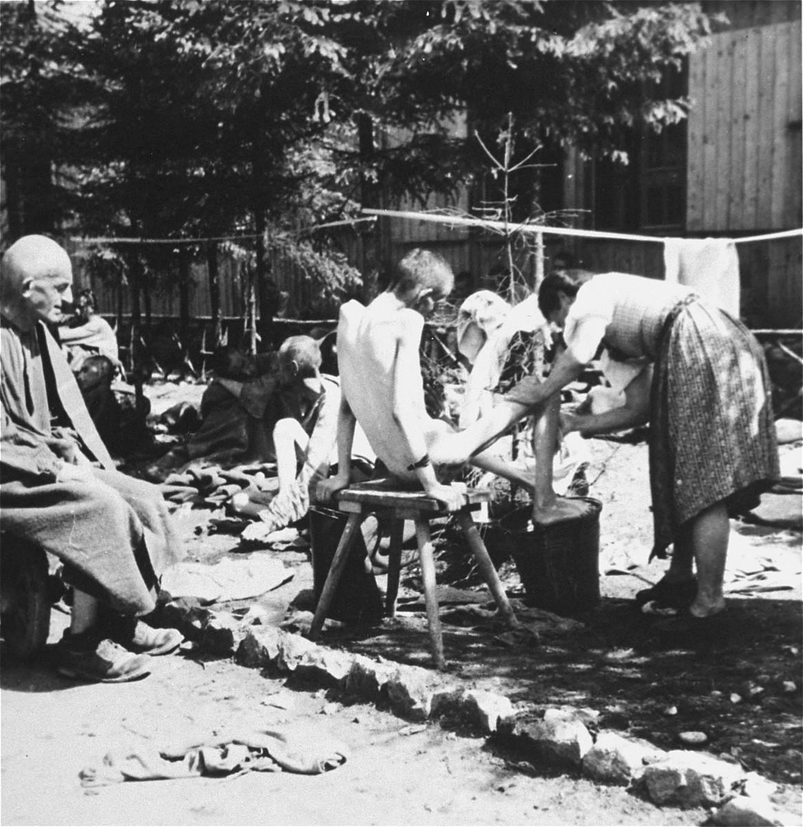 An Austrian woman washes a survivor.