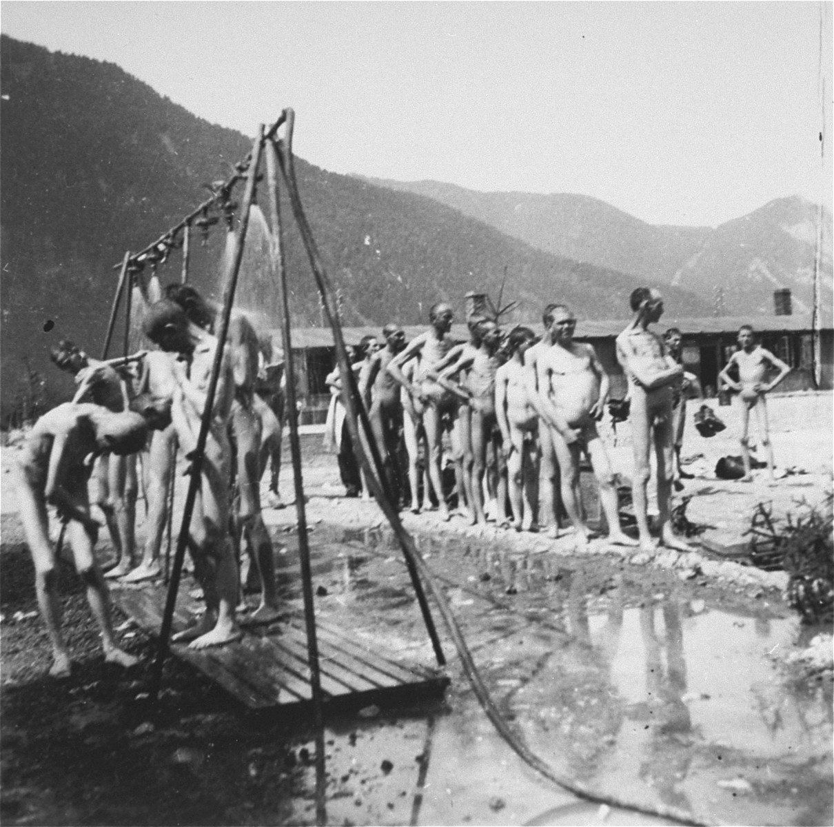 Survivors in Ebensee use the portable shower unit set up for them by personnel of the 30th U.S. Army Field Hospital.