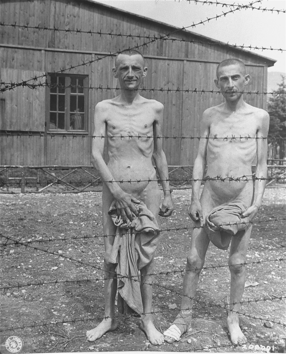 Two emaciated survivors stand behind a barbed wire fence in the hospital compound at the Ebensee concentration camp.