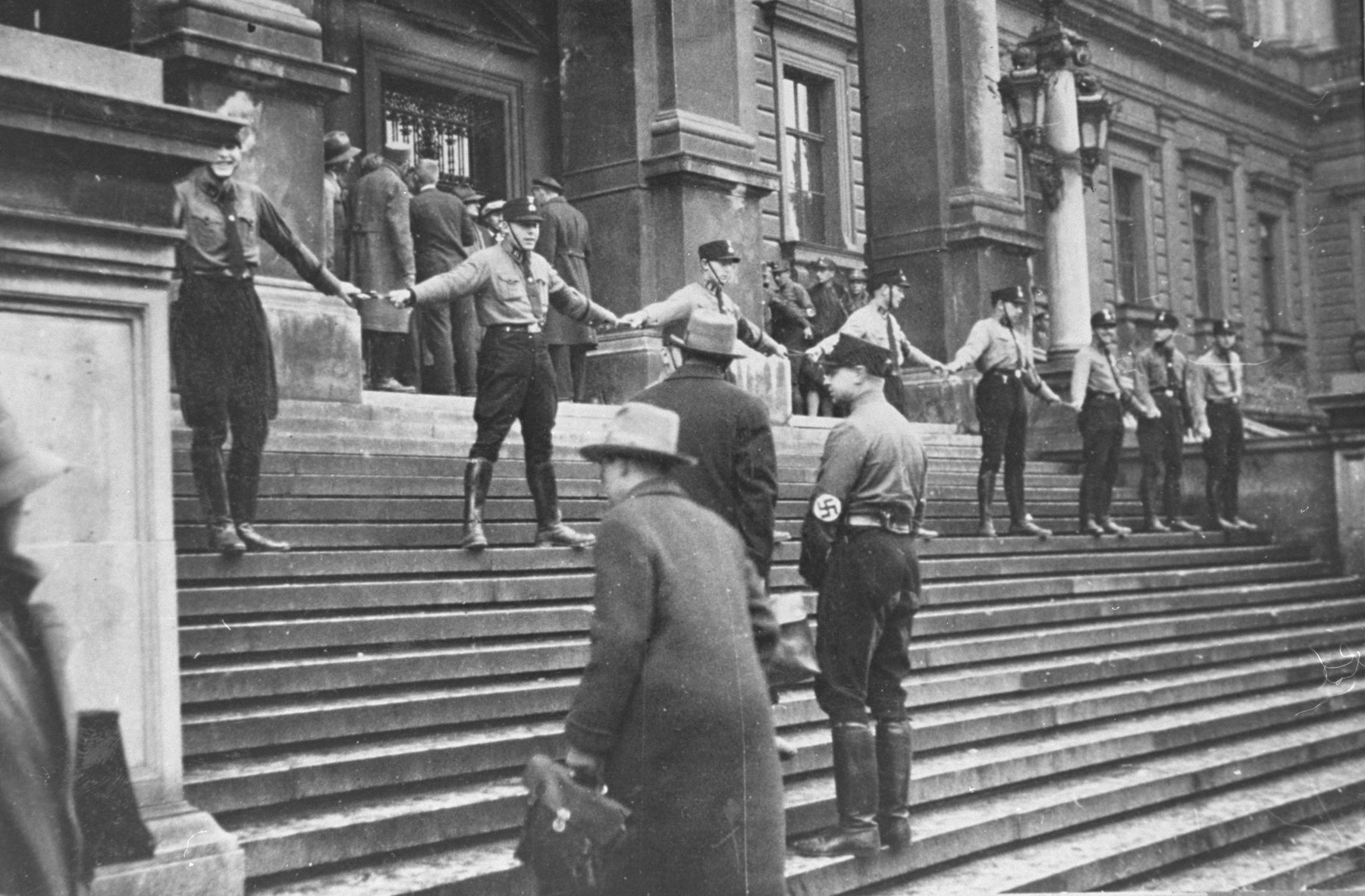 A group of SA hold hands on the steps of the University of Vienna in an attempt to prevent Jews from entering the building.  The action led to a day of student rioting, which had to be suppressed by police.