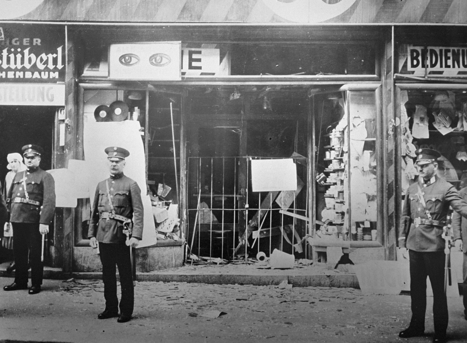 Austrian police stand guard outside a Jewish-owned business damaged in terror bombing by Austrian Nazis.