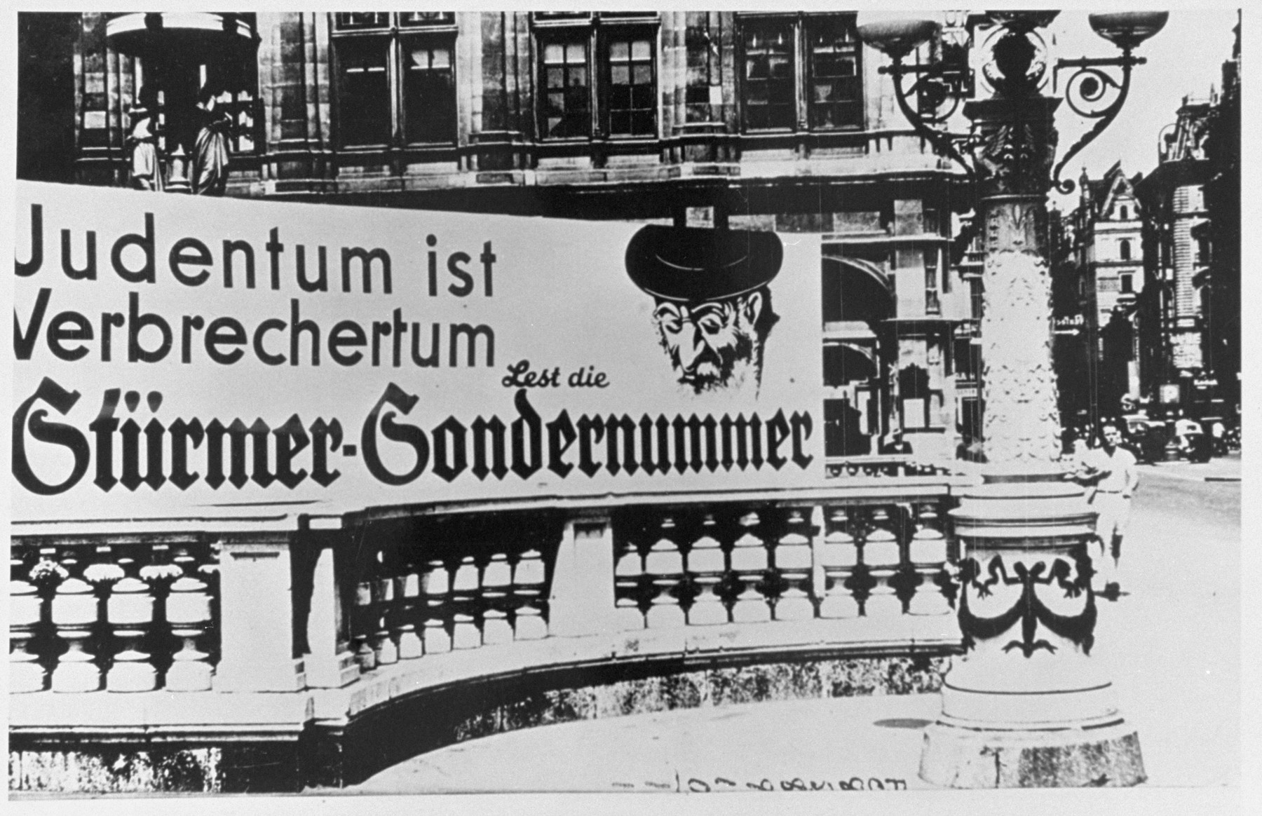 "An anti-Semitic ""Der Stuermer"" advertisement in front of the opera house in Vienna reads: ""To be Jewish is to be criminal.  Read the special edition of Der Stuermer."""