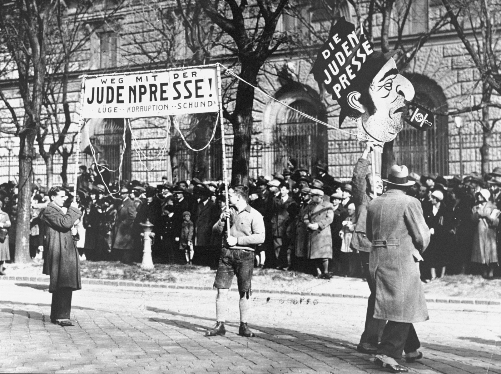 "A large demonstration in Vienna in which 20,000 National-Socialists gathered on the Heldenplatz to protest against the St. Germain and Versailles treaties.  Demonstrators carry banners which read ""Away with the Jewish press: lies, corruption, rubbish."""