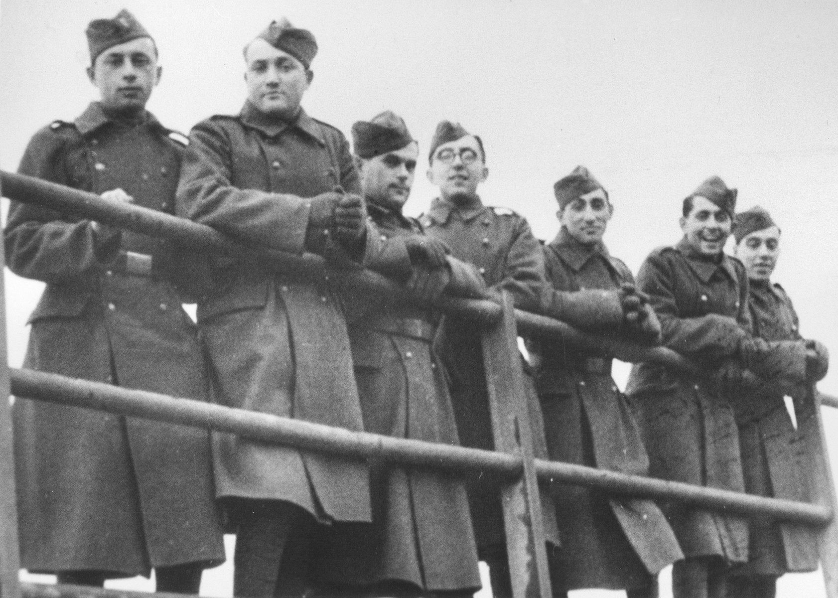Seven Jewish members of the Sixth Labor Battalion (VI Prapor) pose behind a railing at a Slovak labor camp.   Among those pictured is ? Lower (second from right) from Presov, Slovakia.