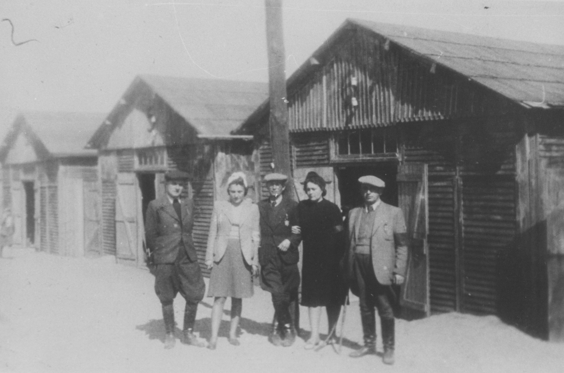 Five Jewish prisoners pose outside a row of barracks at the Belzec concentration camp.