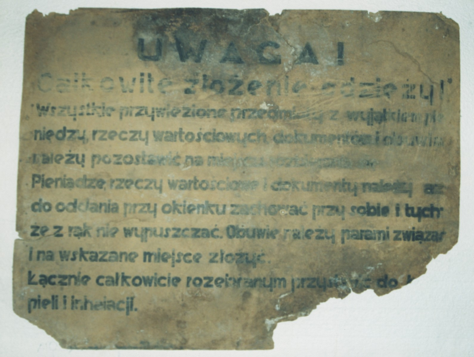"A sign in Polish from the Belzec killing center that reads, ""Attention!  All belongings must be handed in at the counter except for money, documents and other valuables, which you must keep with you.  Shoes should be tied together in pairs and placed in the area marked for shoes.  Afterward, one must go completely naked to the showers."""