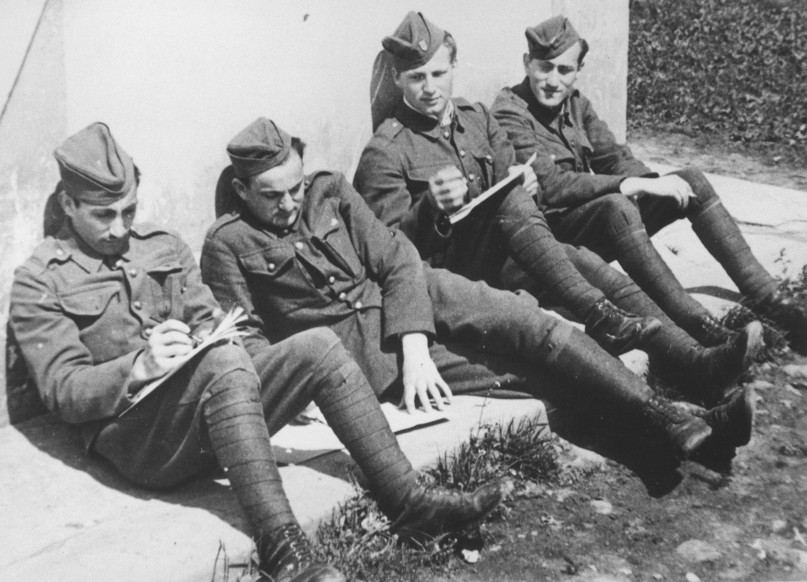 Four Jewish members of the Sixth Labor Battalion (VI Prapor) sit outside a building at a Slovak labor camp.