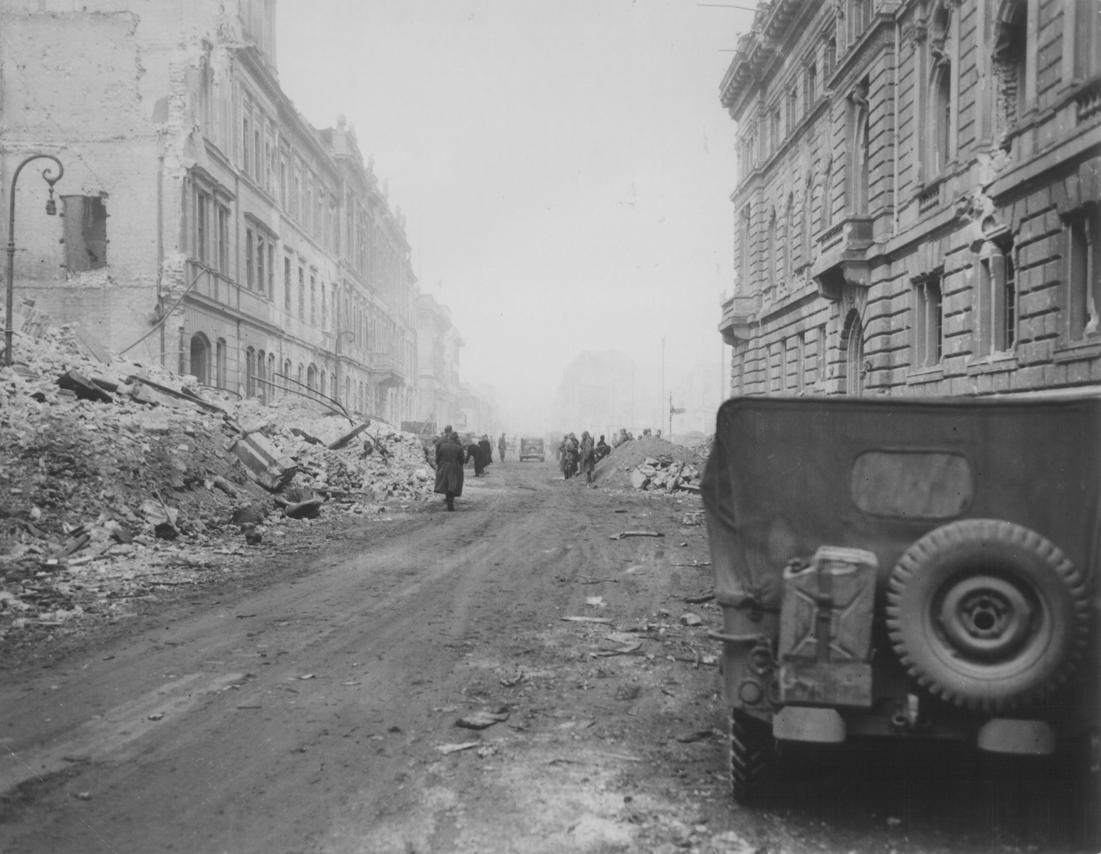 Allied troops walk along a rubble-strewn street in a German city at the end of World War II.