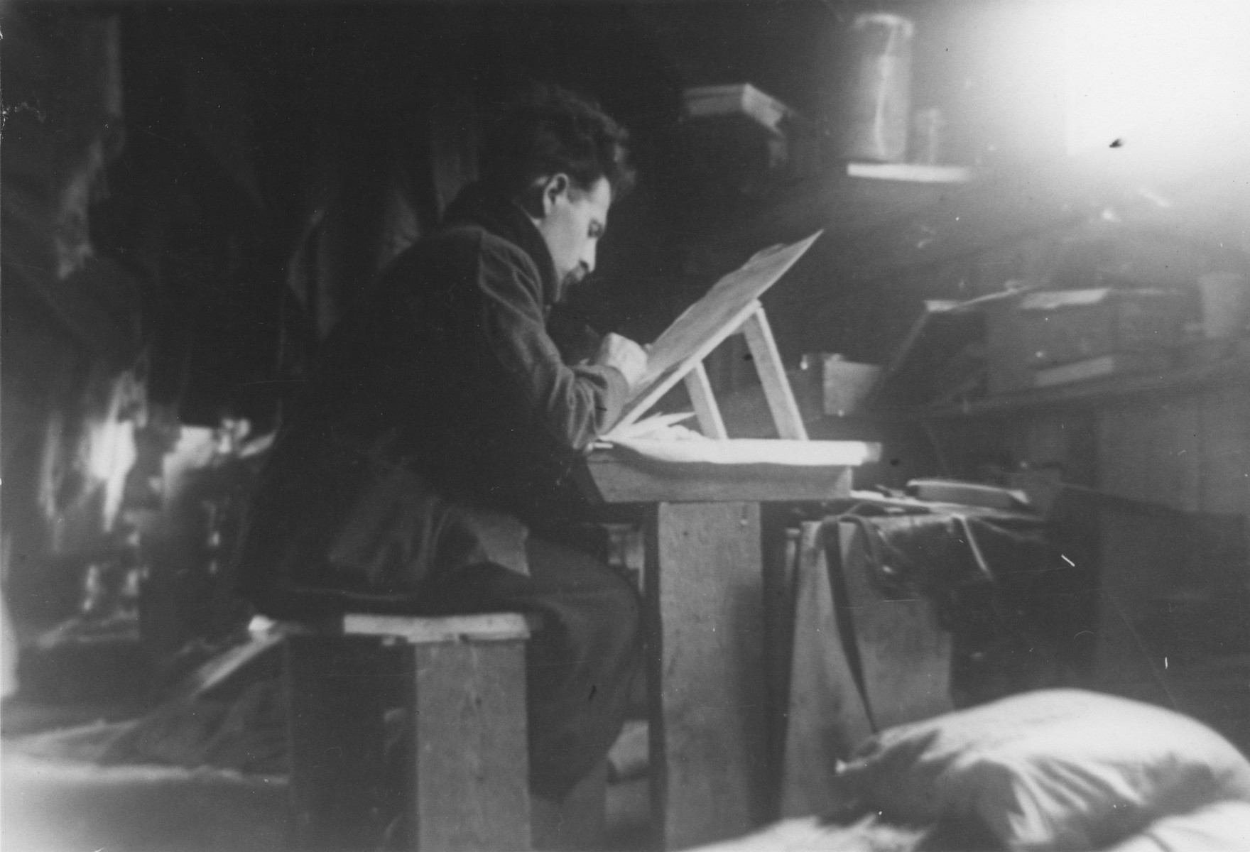 Bill Freier (Willi Spira) works at a small table easel in an unidentified French internment camp.