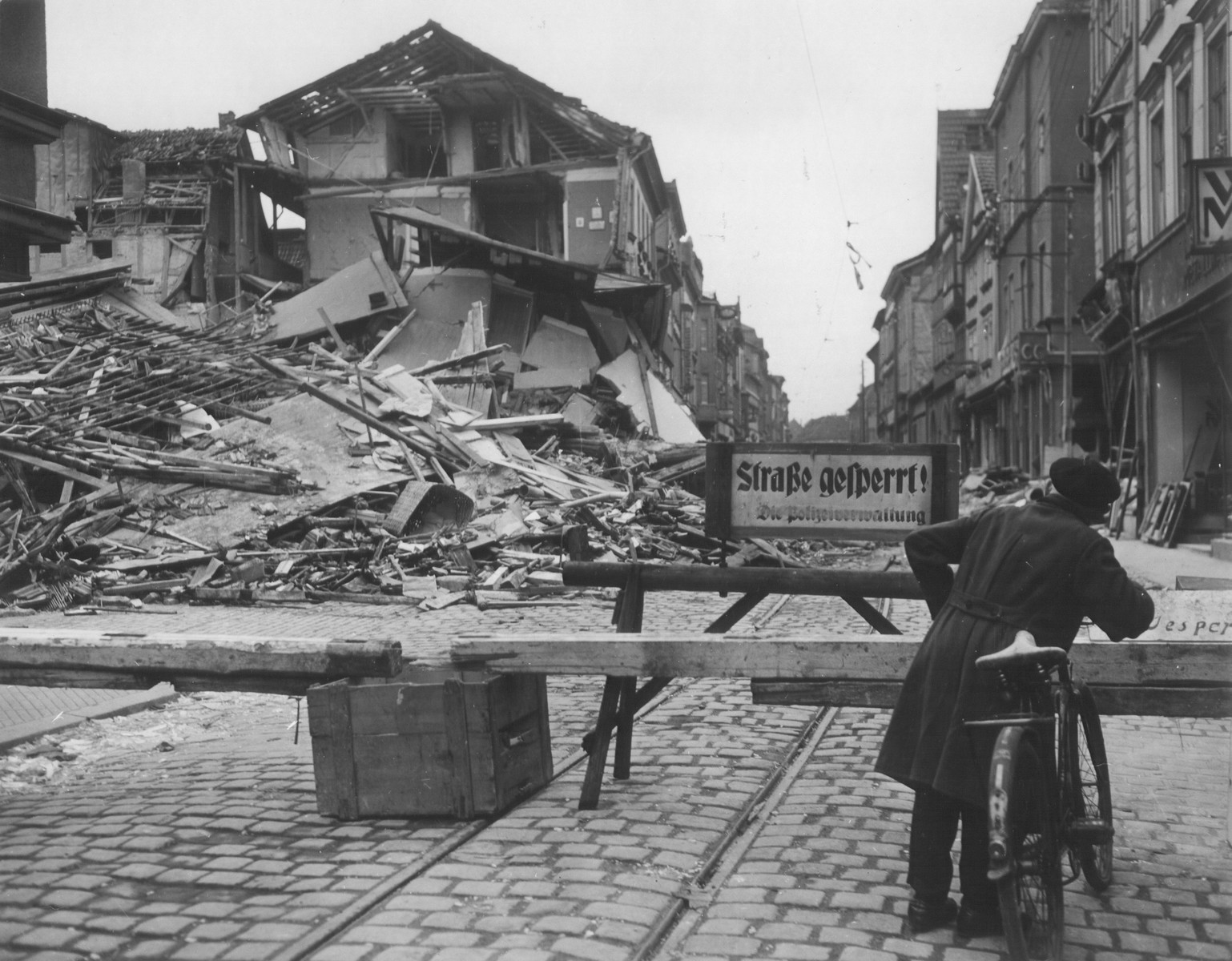"""A boy with a bicycle stands at a barrier closing off a heavily damaged street in a German city.  The German sign on the barrier reads, """"Street closed/ The police authority."""""""