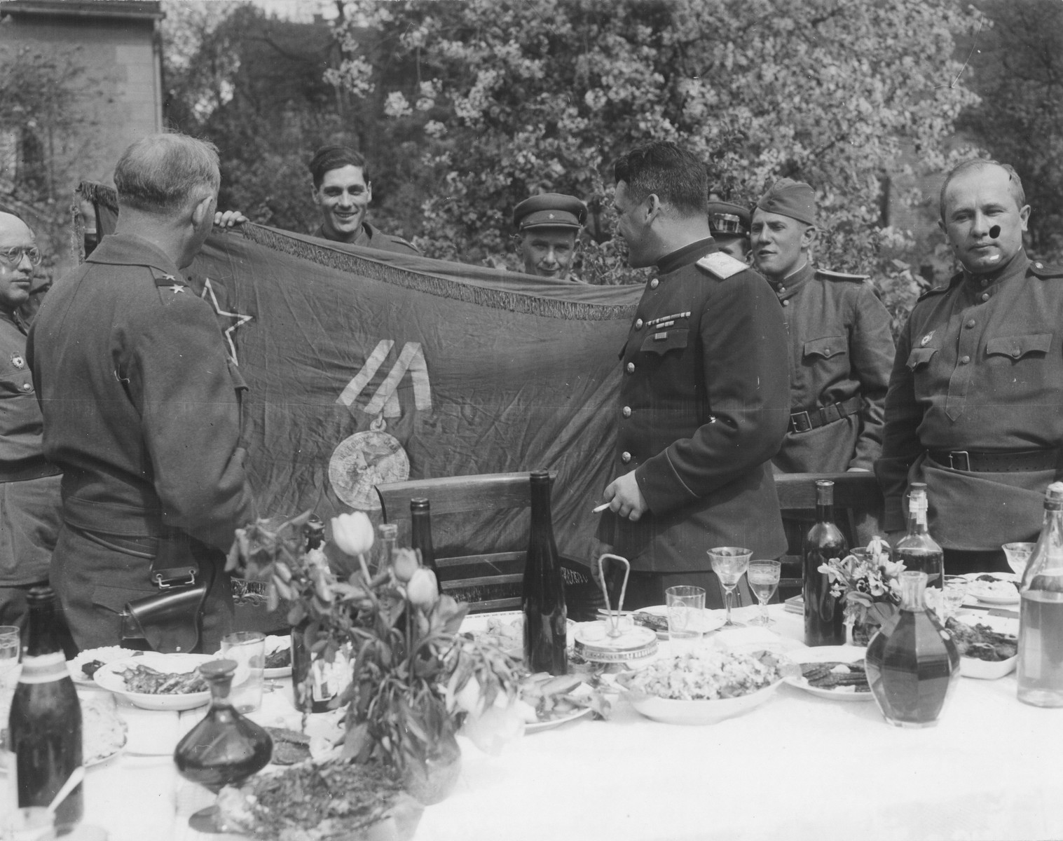 Soviet officers view a large banner featuring the Red Star and a military decoration before sitting down to an outdoor banquet.