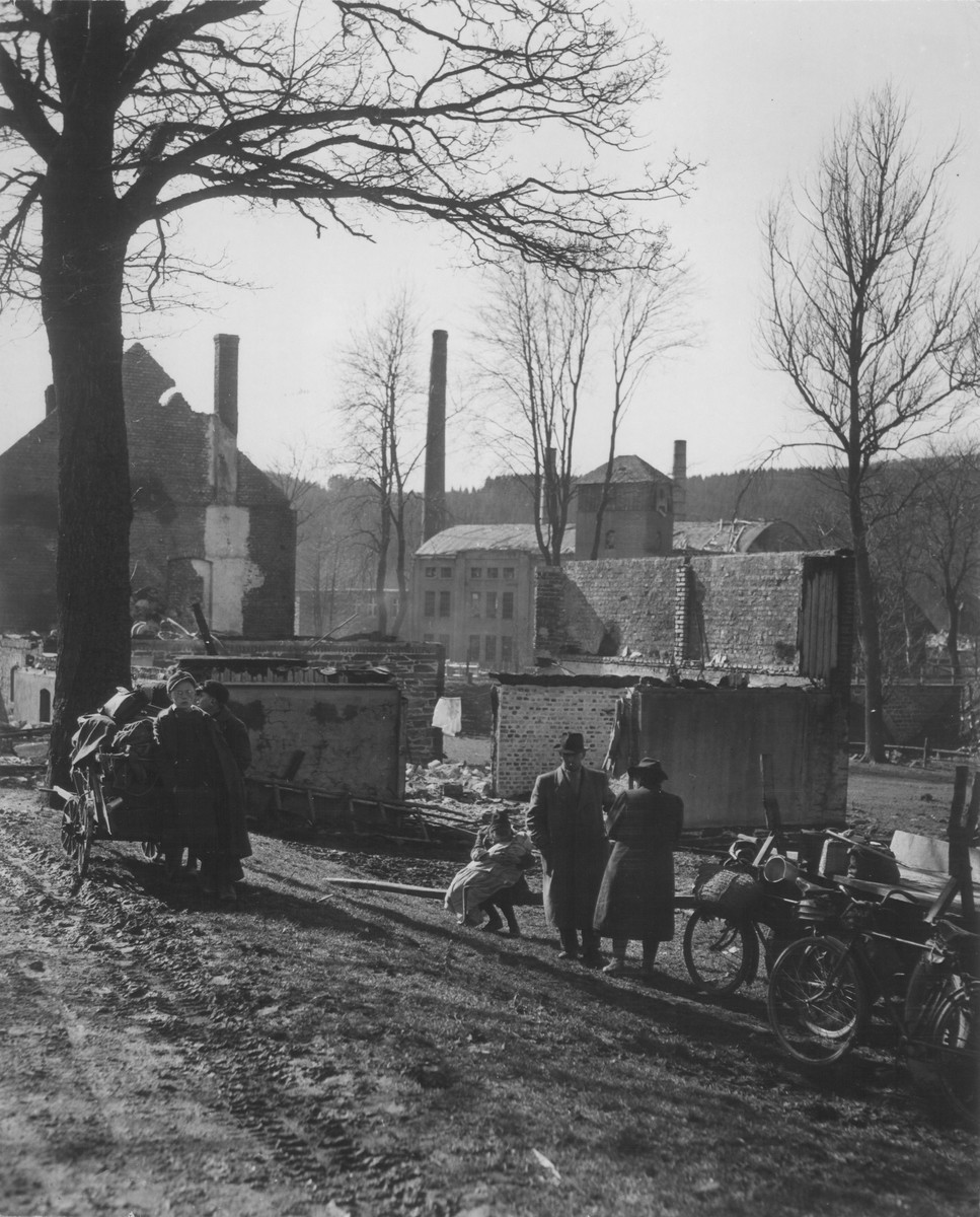 Civilians carting their belongings on carts and bicycles stop in front of a destroyed building in a German town at the end of World War II.