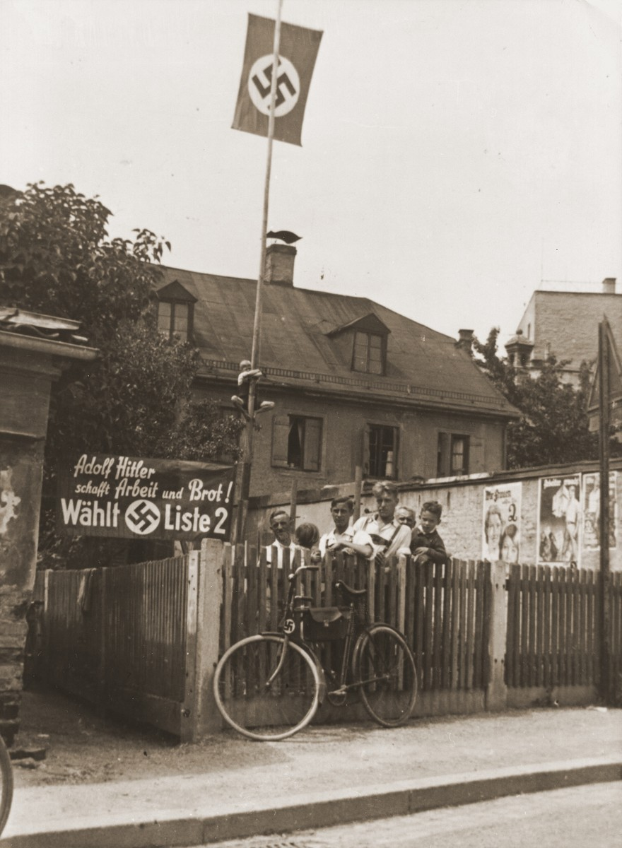 """Young Nazi party supporters stand next to an election poster that reads: """"Adolf Hitler will provide work and bread!  Elect List 2!'  Posted on the wall at the right are posters urging women and workers to support the Nazis."""