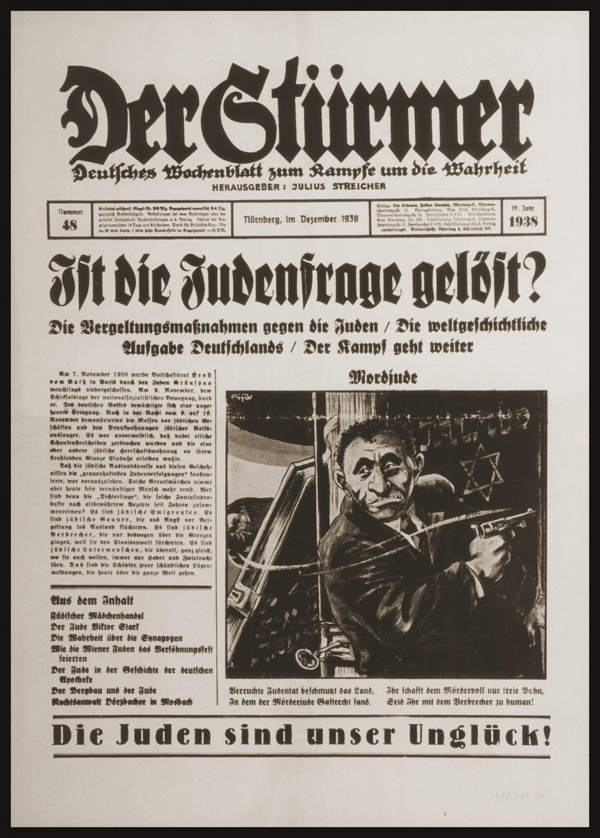 "Front page of the Nazi publication, Der Stuermer, with an anti-Semitic caricature of Herschel Grynszpan, the Jewish assassin of Ernst vom Roth.    The caption reads, ""Jewish Murderer/Despicable Jewish deeds besmirch the land/In which the Jewish murderer was accorded the rights of a guest/You have given the murderous people a free path/If you treat the criminal like a human being!""   The headline reads, ""Is the Jewish question solved:  Retributive measures against the Jews/The world historical task of Germany/The struggle continues."""