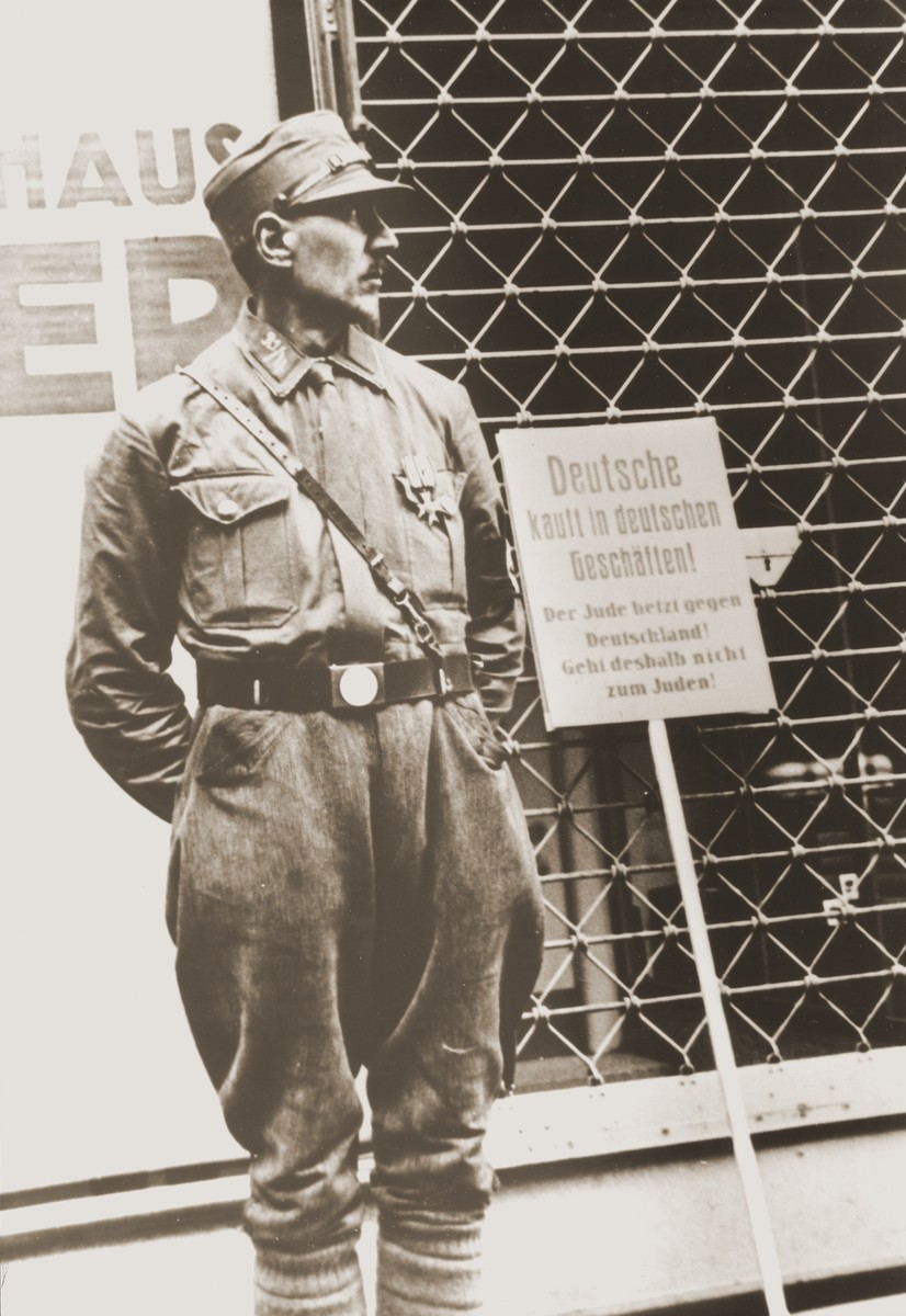 "An SA member stands guard at the entrance to a Jewish-owned store during the April 1, 1933 boycott.  The sign next to him reads: ""Germans shop in German stores!  The Jew is stirring up hate against Germany!  Therefore, do not go to Jewish stores!"""