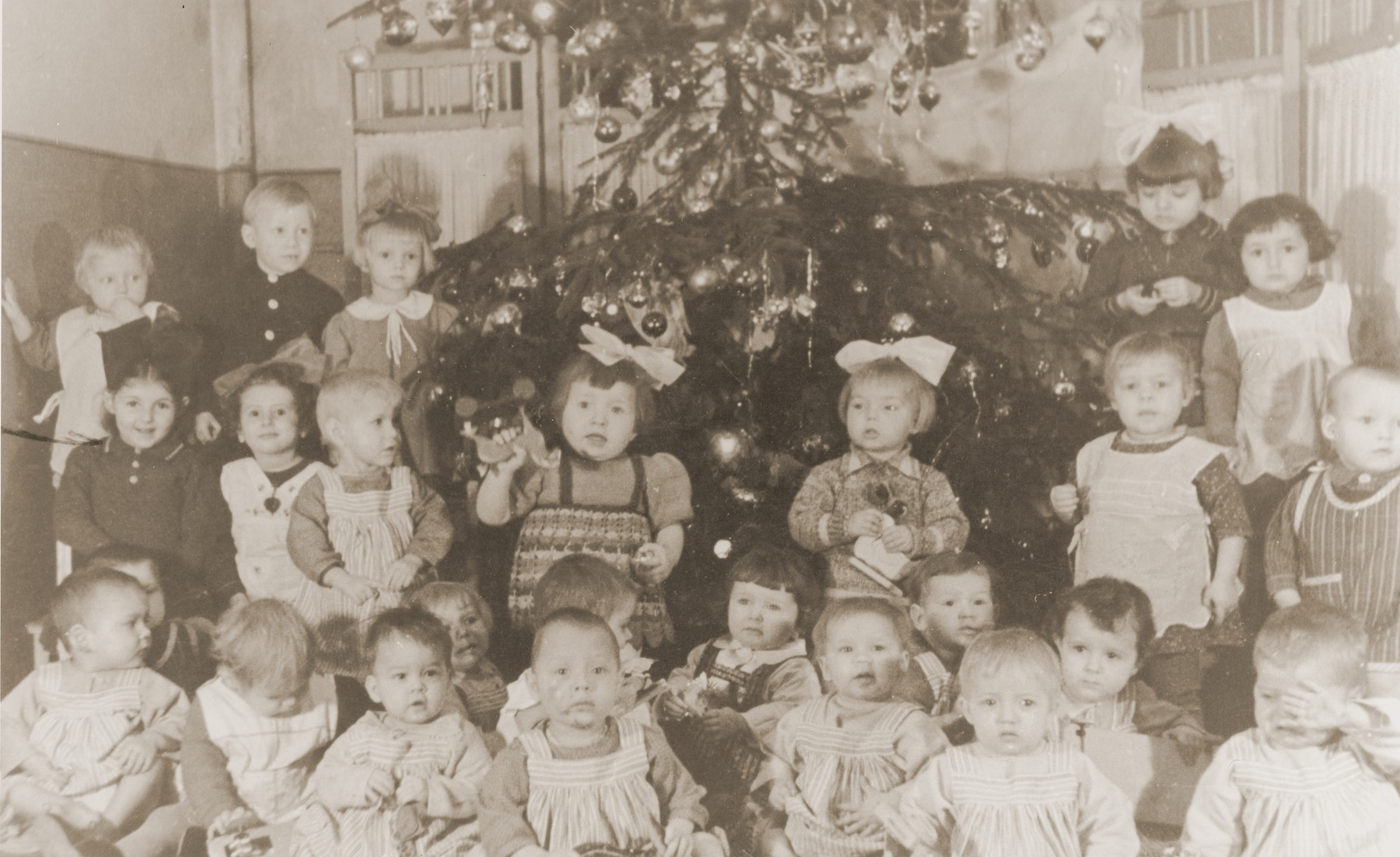 Group portrait of children celebrating Christmas at a Polish orphanage (Dom Dziecka) in Czestochowa.   Among them is Celina Berkowitz (second row, first on the left), a Jewish child in hiding.