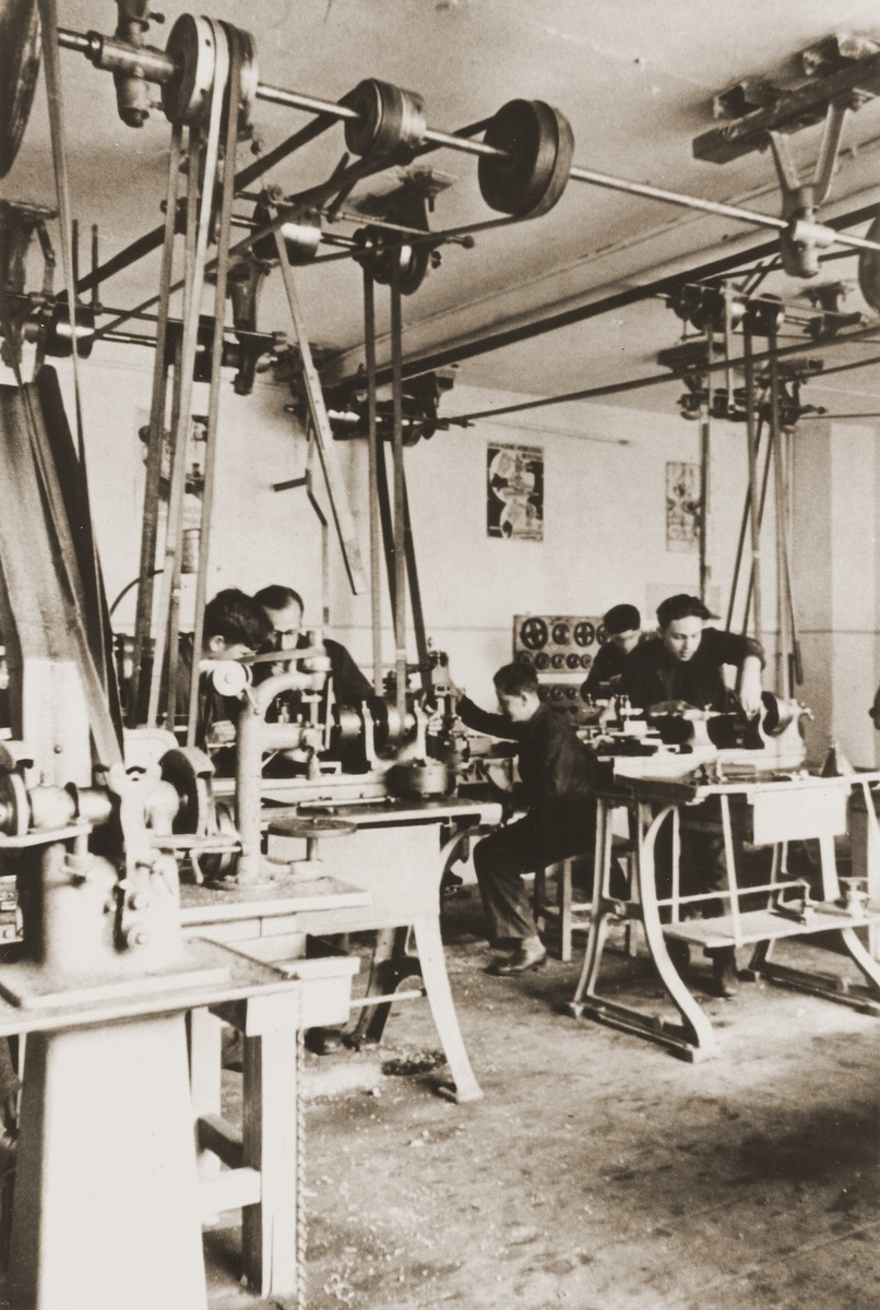 Jewish youth learn woodworking skills at the Juedische Anlehrnwerkstatt [Jewish vocational training school].  Harry Loeb is pictured in the center at the wood shaver.  The Juedische Anlehrnwerkstatt was founded in 1936 by the Frankfurt Jewish community to train young Jews expelled from the German public schools.