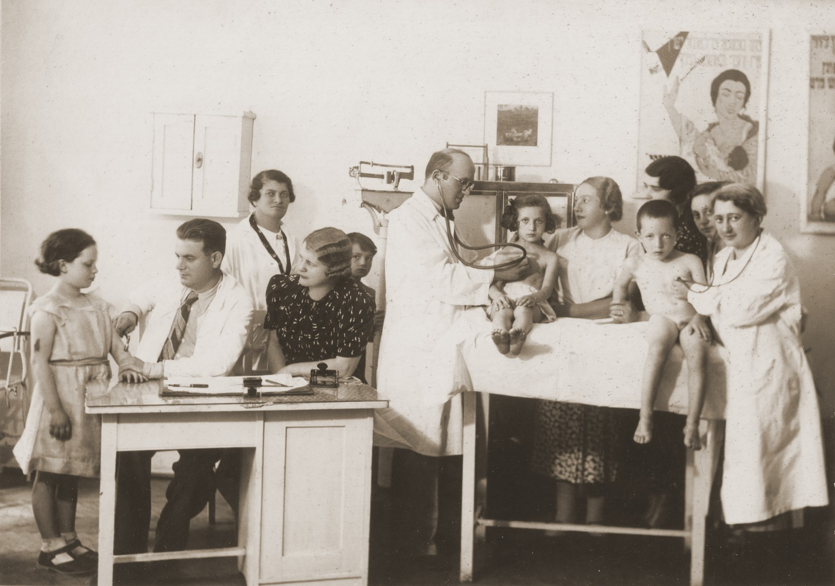 Doctors and nurses examine children in a pediatric clinic in Cernauti.    Among those pictured are Dr. Mendel Wiesenthal (center), Cernauti's most prominent Jewish pediatrician; Josephina Metsch Appenzeller (the donor's mother, who is looking at Wiesenthal); and Dr. Salick, a female pediatrician (far right).   The Yiddish poster on the wall, printed by OSE (Oeuvre secours aux enfants) extols the virtues of breast-feeding.
