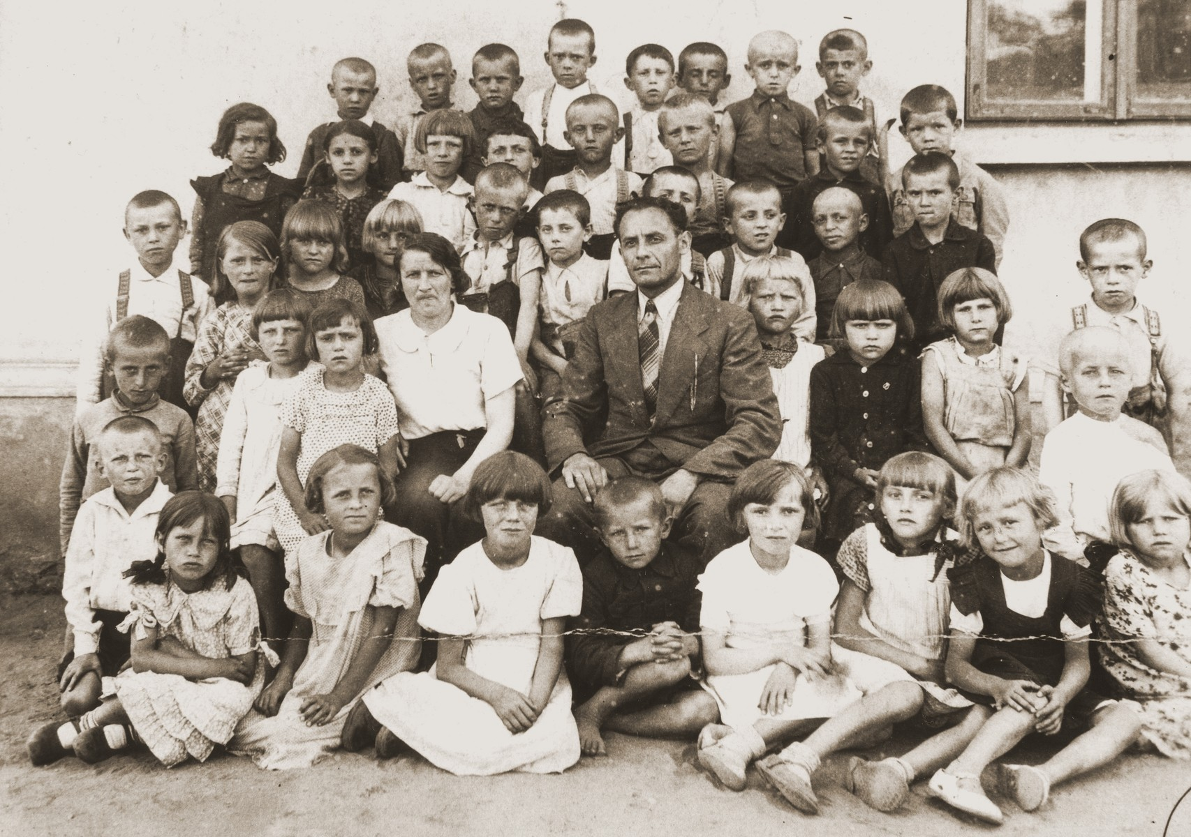 Class portrait of first grade students at a public school in Klobuck.    Abram Gelbart, the donor's husband, is pictured in the top row, second from the right.