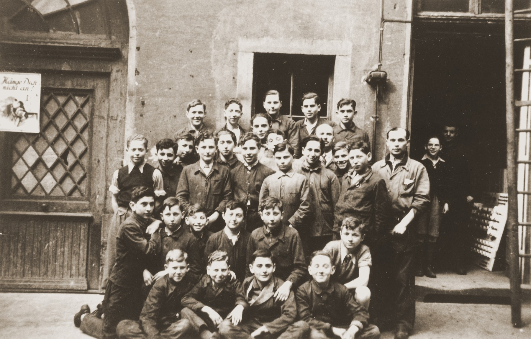 Group portrait of Jewish youth in the keymaker's course at the Juedische Anlehrnwerkstatt [Jewish vocational training school].  Harry Loeb is pictured in the second row from the front, third from the right.  The Juedische Anlehrnwerkstatt was founded in 1936 by the Frankfurt Jewish community to train young Jews expelled from the German public schools.