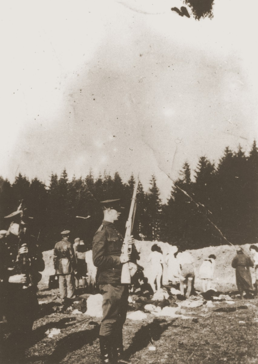 Members of a Lithuanian militia unit force a group of Jewish women from Panevezys to undress before their execution in the Pajuoste Forest.