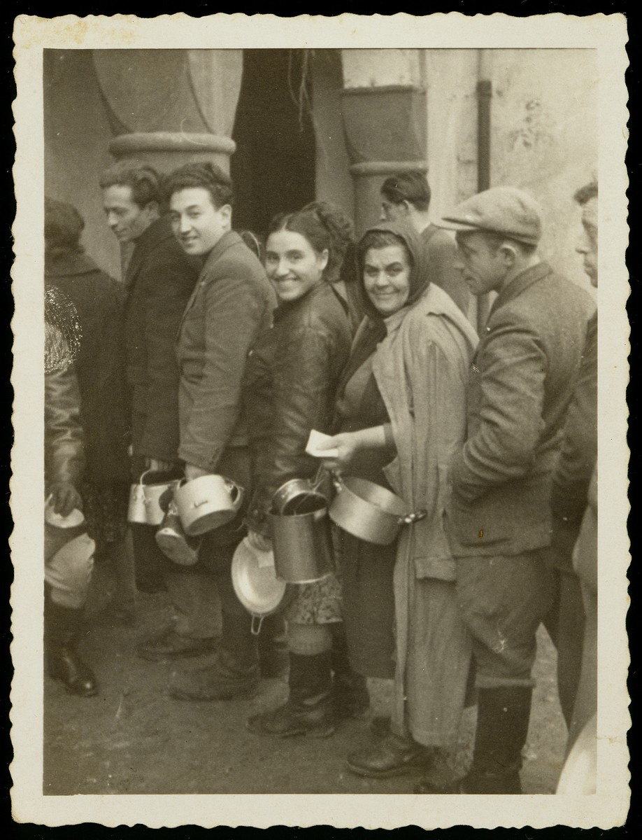 A group of Polish Jews waits in line with lunch pails [probably in Eisiskes].