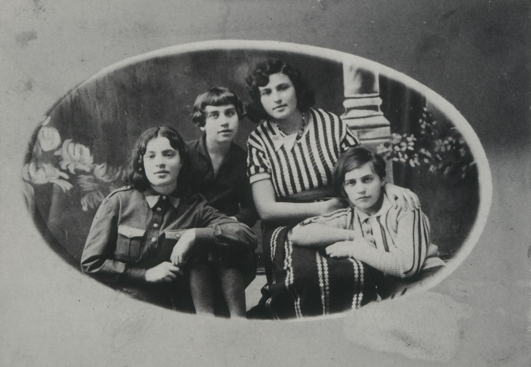 Studio portrait of the Edelstein family.  Top row, right to left: two cousins, Freedah Edelstein and Liebaleh Belicki; leaning on her cousin Rochella Belicki, and sitting on the left is Batsheva Edelstein, a sister of Freedah. Freedah was born in 1911. She, her husband, and children were murdered in the September 1941 massacre in Eisiskes.  The other three girls were also murdered during the Holocaust. Bat-Shevah was murdered with her fiancee.