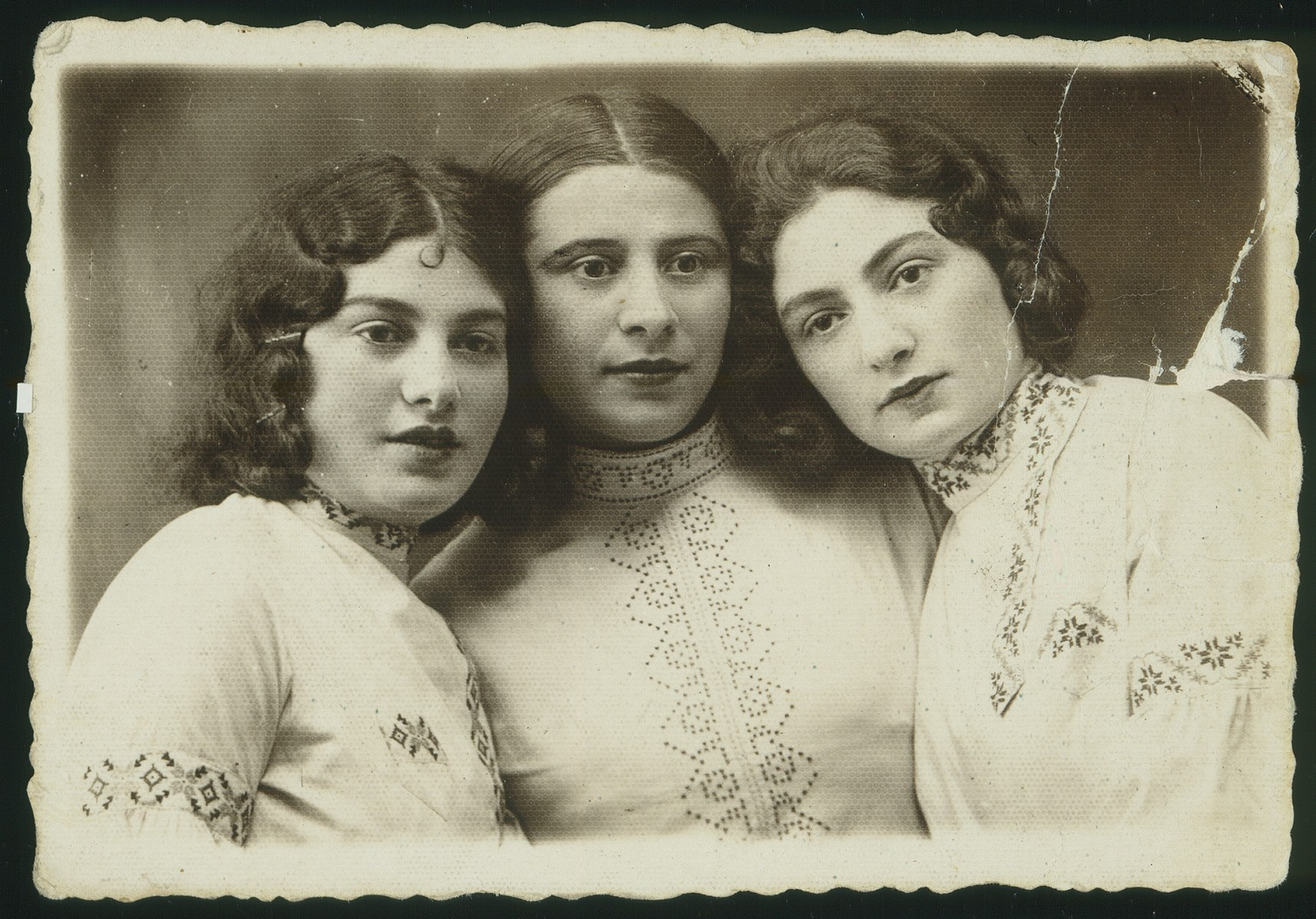 Portrait of three young women wearing embroidered shirts.   From right to left: Batia Lubetski, Hayya Gruznik Dworkin and Bluma Lubetski.  Batia Lubetski and Hayya Gruznik Dworkin immigrated to Palestine, and  Bluma Lubetski survived the Holocaust in Russia.