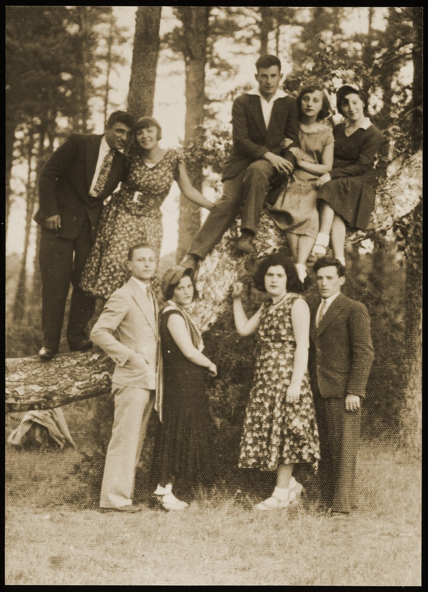 Young couples go for a walk in the Seklutski forest, outside of Eisiskes.   Among the friends are Szeina Blacharowizc (seated on the branch, right) ; Malka Matikanski with her boy-friend Zahavi (standing on the branch, second from left) ; Miriam Koppelman (standing first row, second from right).