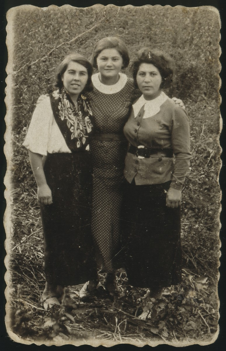 """Three women pose together outside.  Right to left: Goltke Ginunski, the daughter of Rivl """"Aranerke"""",  and Altke Paikowski. Altke and Goltke were murdered during the Holocaust."""