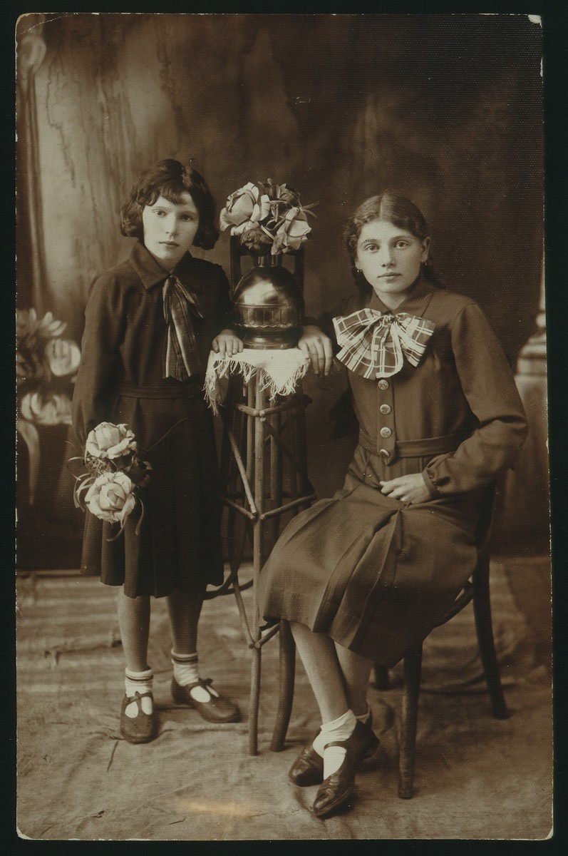 Studio portrait of two sisters.  Rivka Dubczanski is pictured on the right, and her sister, Masha, is on her left.  Both Dubczanski sisters were murdered by the Germans during the September 1941 mass killing action in Eisiskes.