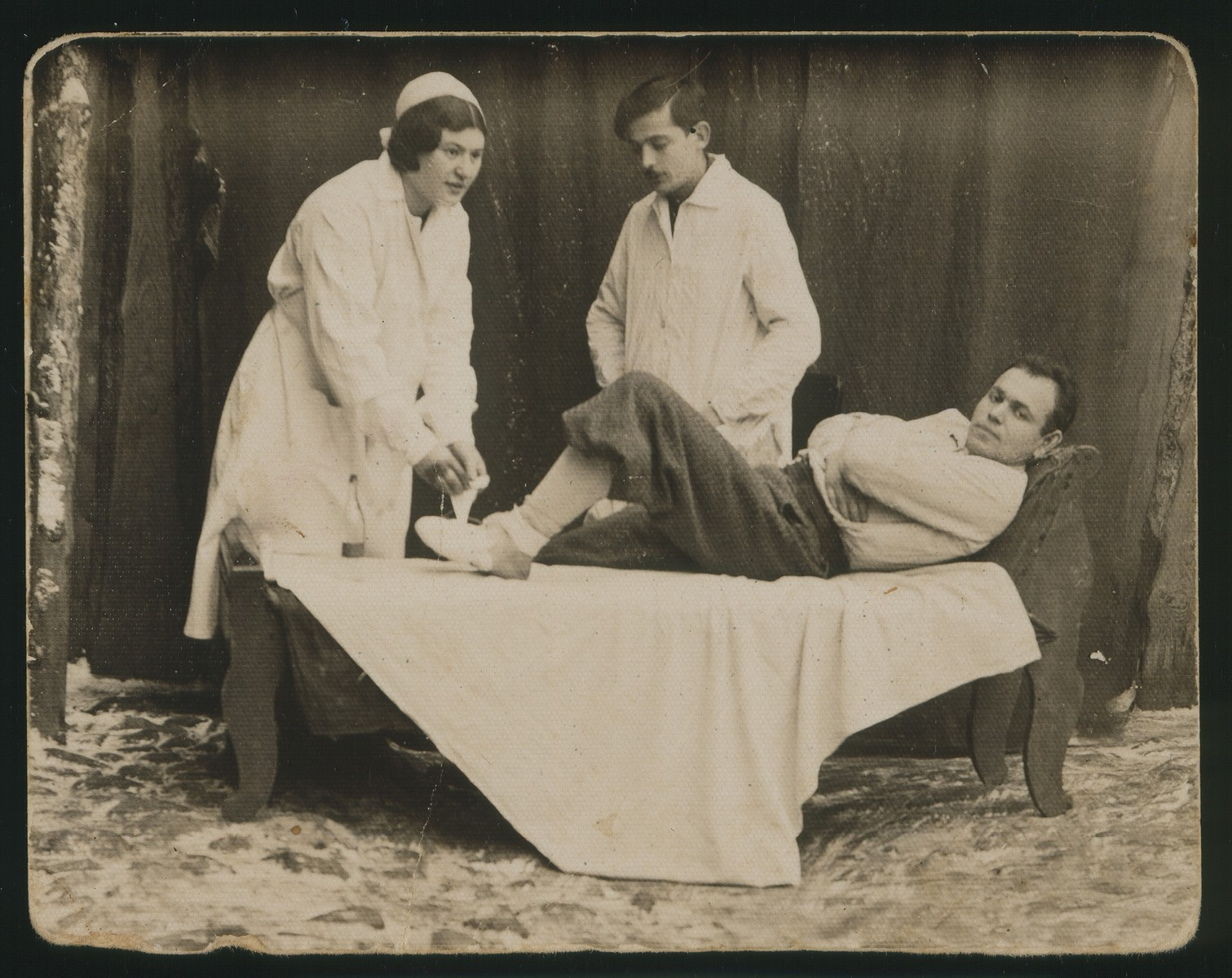 Sara Plotnik, who studied nursing in Vilna, bandages the leg of a friend.