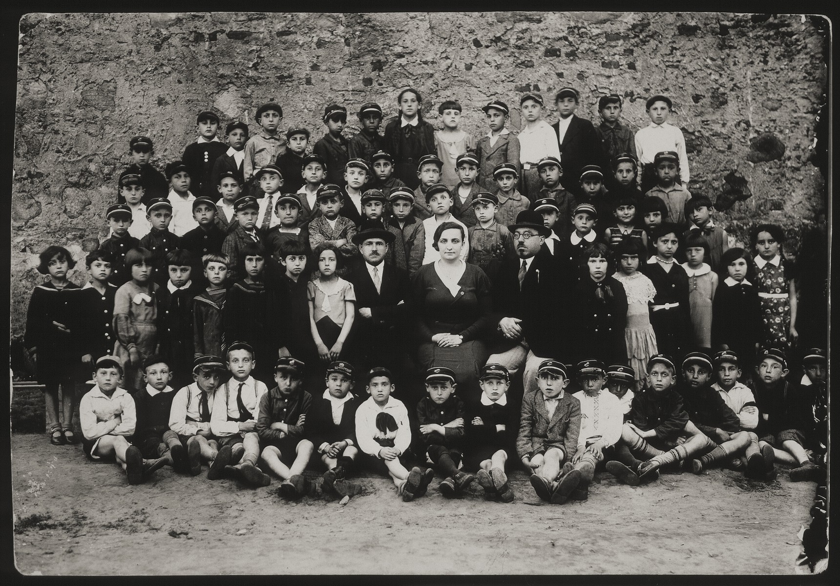 Group portrait of the elementary school in Eisiskes.   First row (sitting on the floor): Avigdor Katz (first from left), Moshe Bastunski (eighth from left) Avremele Botwinik, son of the principal (ninth from left). Second row from bottom: Rochel (far right), Rivka Dubchansky (sixth from right), Leah Tawlitski (fifth from right), Dora Kremin Dimitro (fourth from left). Sitting right of the female teacher is Shael der Lehrer.  To her left (wearing hat and glasses) is Principal Botwinik. Third row from bottom: Leibke Remz (fifth from left), Leibke Kaganovicz (Leon Kahn, sixth from left). Second row from top: Zvi Michalowski (fifth from right). Top row: Rivka Pushkin Cofnas (seventh from right).   Dora, Leibke, Zvi, Avremel all survived the Holocaust in the forests. Rivka survived the Holocaust in Russia.  All others were murdered during the Holocaust.