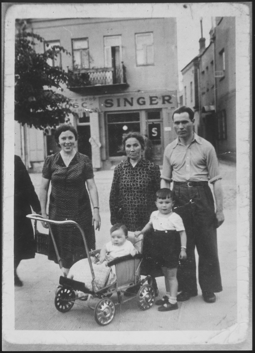 The Ejszyszki family poses on a commercial street in Eisiskes.  Those pictured are Gedaliah Ejszyszki, his wife Chaya, mother-in-law and children.