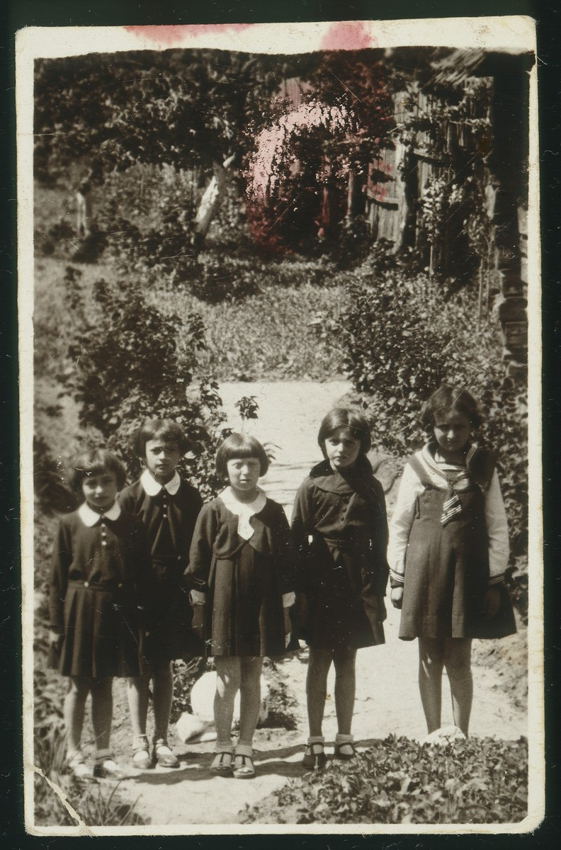 Five school girls pose in a garden in Eisiskes.    Standing at the far right is Altke Koutsai.  Standing at the far left is Sheinele Dwinlanski and second from left is Leah Michalowski.  All the girls were murdered during the Holocaust.