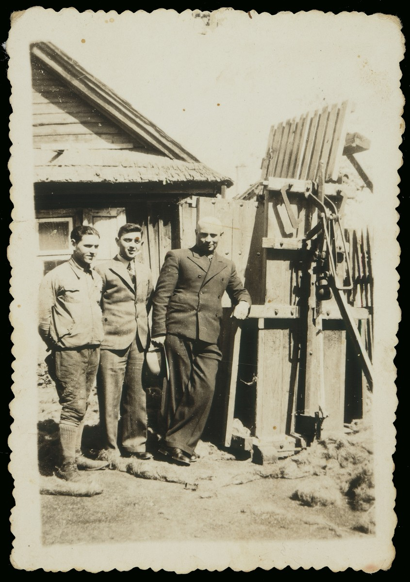 Mr. Derebiacki stands outside his linen factory with Pesach Avrahami and another youth.