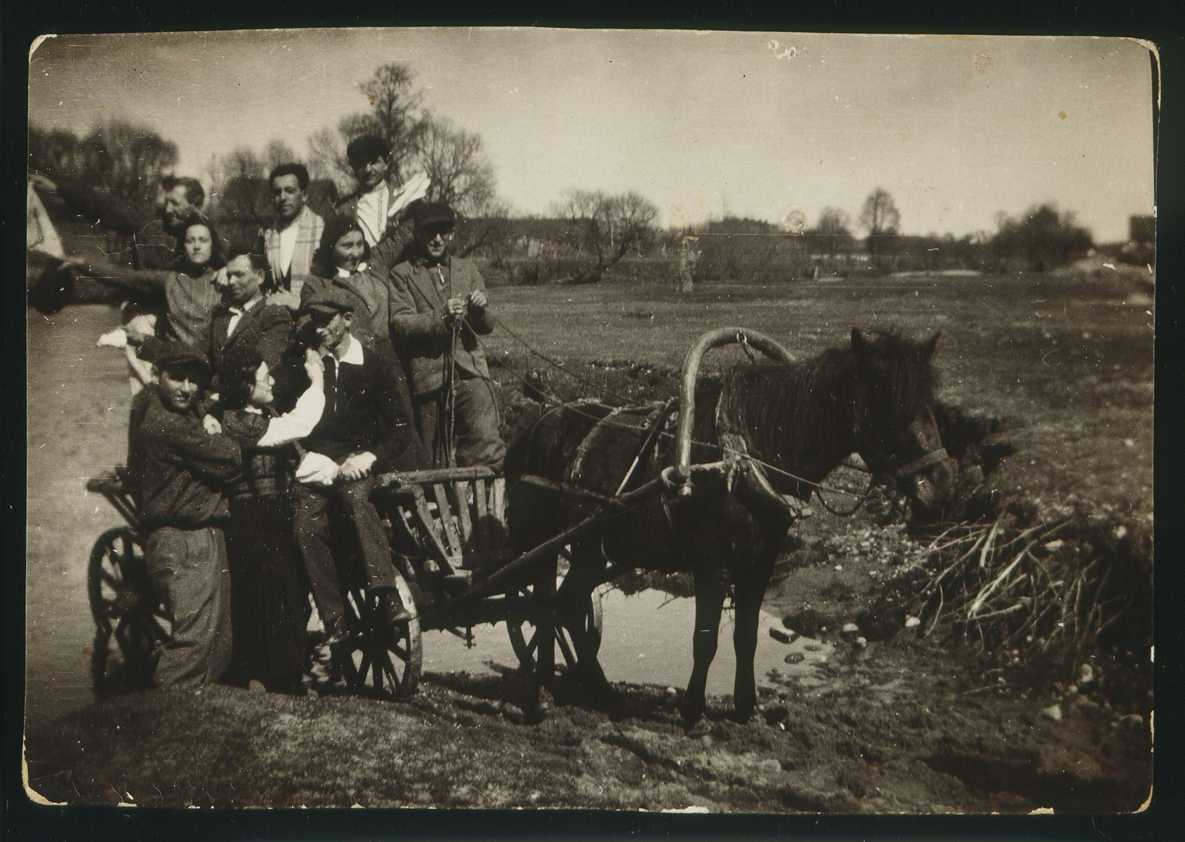 Members of a Hehalutz Zionist hachshara in Oszmiana on a horse-drawn cart.   Sara Plotnik is standing on the side of the cart and Yehiel Blacharowicz is in the back at the far left.  Sara and Yehiel were from Eisiskes.  Yehiel did not receive an immigration certificate to Palestine and was murdered in the September 1941 massacre. The fate of the others is unknown.