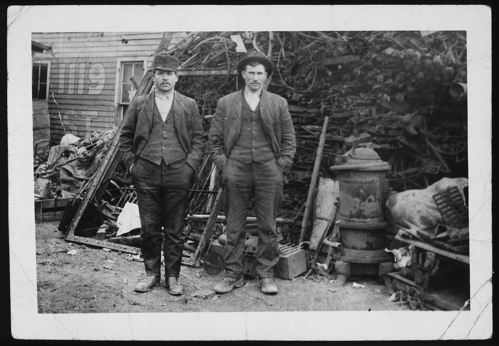 Morris (right) and Yitzhak Asner stand in front of a pile of scrap metal.