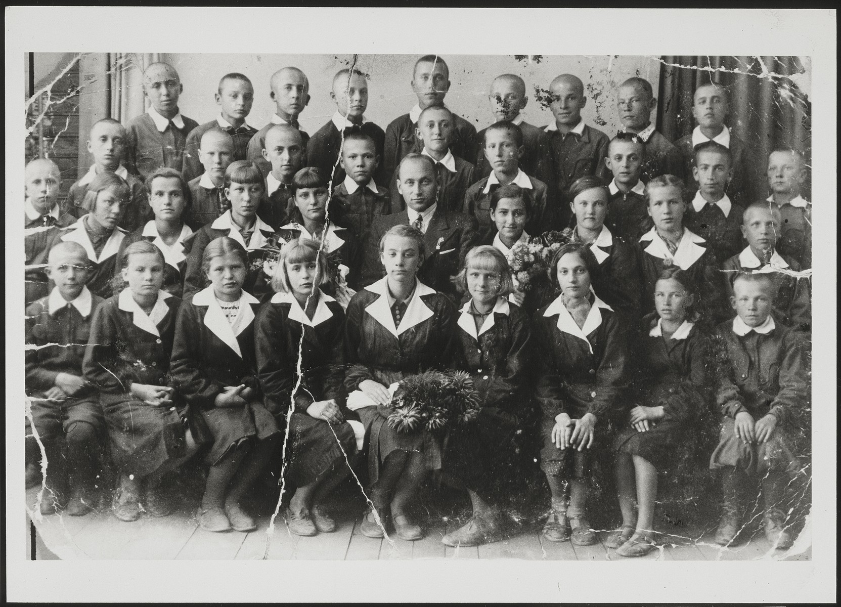 Polish and Jewish children in the Polish public school in Eisiskes.   Second row from top: second from right is Shlomo Tevke Paikowski; third from right is Leon Kahn, fifth from right is Shmuel Sovitzky (behind the teacher). Third row from top: teacher Antonovicz is sitting in the center (he was a member of the Polish Home Army).  Hayya Levitan (second row from bottom, fourth from right) Front row, third from right is Menuha Michalowski.   Leon Kahn survived the Holocaust. All the other Jewish children were murdered during the Holocaust.